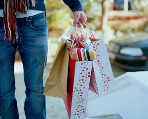 Man holding gift bags --- Image by © Ocean/Corbis